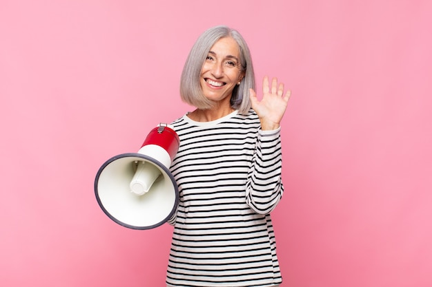 Middle age woman smiling happily and cheerfully, waving hand, welcoming and greeting you, or saying goodbye with a megaphone