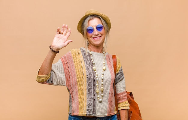 Middle age woman smiling happily and cheerfully, waving hand, welcoming and greeting you, or saying goodbye