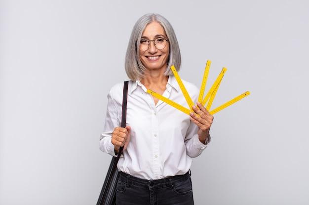 Женщина среднего возраста счастливо улыбается, положив руку на бедро и уверенно, позитивно, гордо и дружелюбно. концепция архитектора