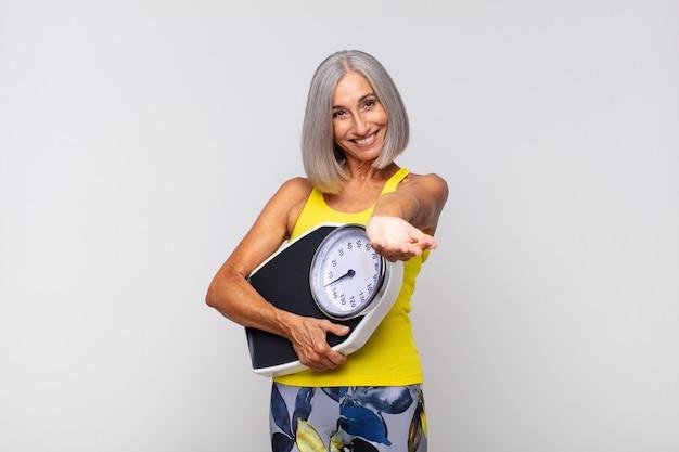 친절하고 자신감 있고 긍정적 인 표정으로 행복하게 웃고 물건이나 개념을 제공하고 보여주는 중년 여성. 피트니스 개념