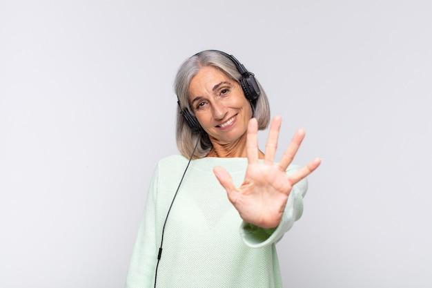 Middle age woman smiling and looking friendly, showing number five or fifth with hand forward, counting down. music concept