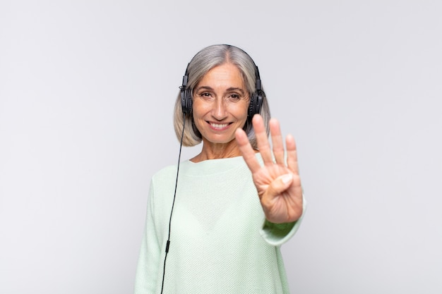Middle age woman smiling and looking friendly, showing number four or fourth with hand forward, counting down. music concept