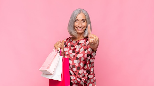 Middle age woman smiling and looking friendly, showing number one or first with hand forward, counting down with shopping bags