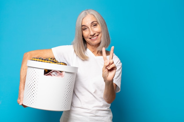 Middle age woman smiling and looking happy, carefree and positive, gesturing victory or peace with one hand