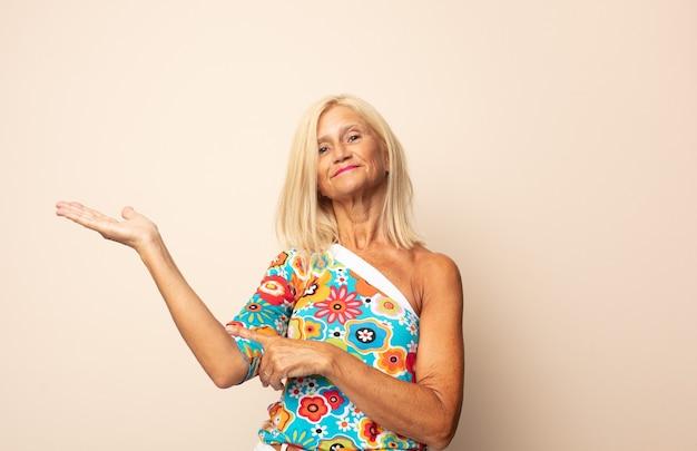 자랑스럽고 자신있게 웃고 행복하고 만족스럽고 복사 공간에 대한 개념을 보여주는 중년 여성