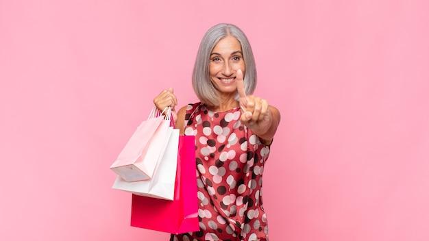 買い物袋を持ったリーダーのように、誇らしげに自信を持って笑顔でナンバーワンのポーズをとる中年女性