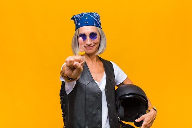 Женщина среднего возраста, гордо и уверенно улыбаясь, торжествующе принимает позу номер один, чувствуя себя лидером