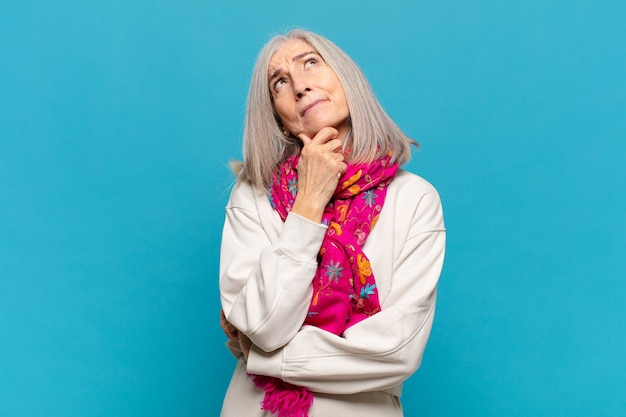 Женщина среднего возраста думает, чувствует себя сомнительно и растерянно, с разными вариантами, задается вопросом, какое решение принять