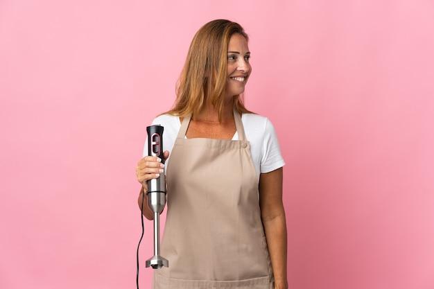 Женщина среднего возраста, использующая ручной блендер, изолирована на розовой стороне