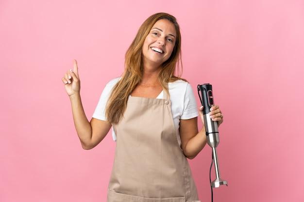 분홍색 벽에 고립 된 핸드 블렌더를 사용하여 중년 여성이 표시하고 최고의 기호에 손가락을 들어 올립니다.