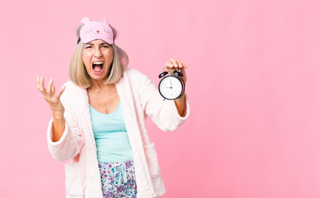 Middle age woman wearing night suit with an alarm clock