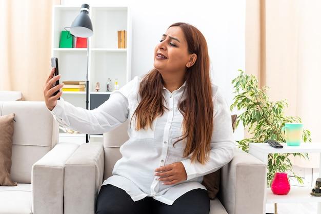 Donna di mezza età in camicia bianca e pantaloni neri che fa selfie utilizzando smartphone felice e fiducioso seduto sulla sedia nel soggiorno luminoso