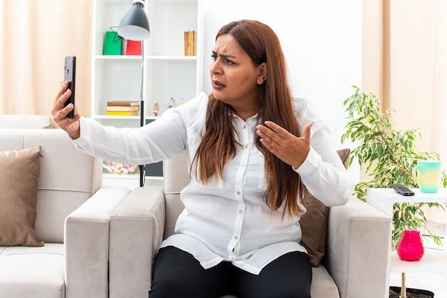 Donna di mezza età in camicia bianca e pantaloni neri che ha videochiamata utilizzando smartphone cercando confuso e scontento seduto sulla sedia in soggiorno luminoso