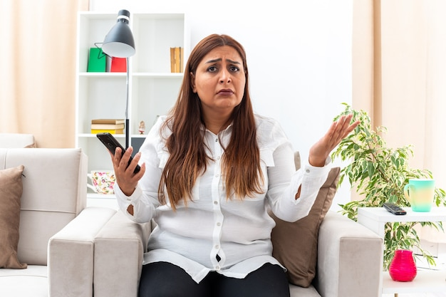Donna di mezza età in camicia bianca e pantaloni neri con smartphone confusa e dispiaciuta seduta sulla sedia in un luminoso soggiorno