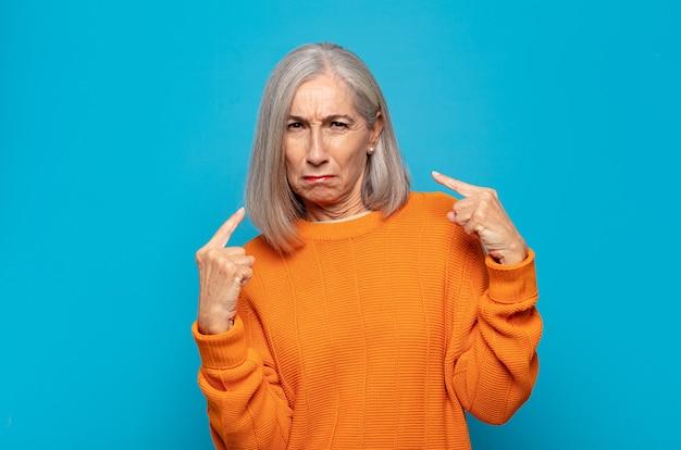 Женщина среднего возраста с плохим отношением выглядит гордо и агрессивно, указывая вверх или весело жестикулируя руками