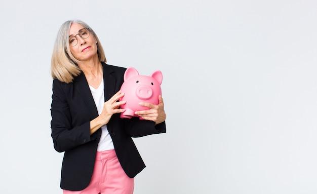 貯金箱を持つ中年女性。貯蓄コンセプト