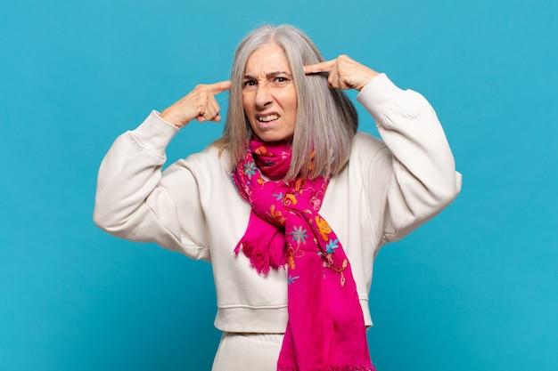 Женщина среднего возраста с серьезным и сосредоточенным взглядом, мозговой штурм и размышления о сложной проблеме