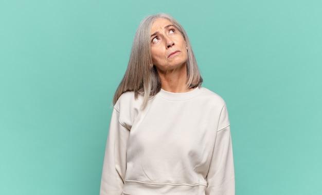 心配、混乱、無知な表情、コピースペースを見上げて、疑っている中年女性