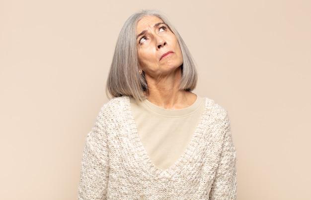 Женщина среднего возраста с обеспокоенным, сбитым с толку, невежественным выражением лица, глядя вверх, чтобы скопировать пространство, сомневаясь