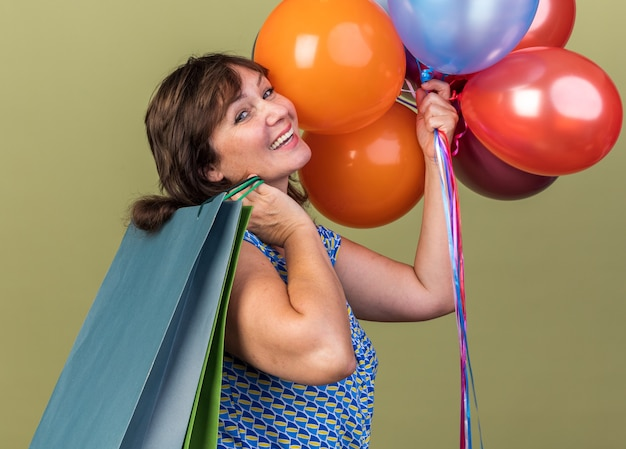 Donna di mezza età con un mazzo di palloncini colorati che tengono sacchetti di carta con regali felici ed emozionati che celebrano la festa di compleanno in piedi sul muro verde green