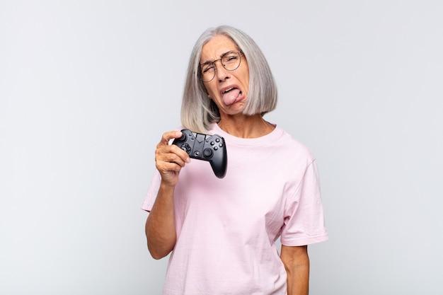 Женщина среднего возраста с веселым, беззаботным, бунтарским настроем, шутит и высунула язык, веселится. концепция игровой консоли