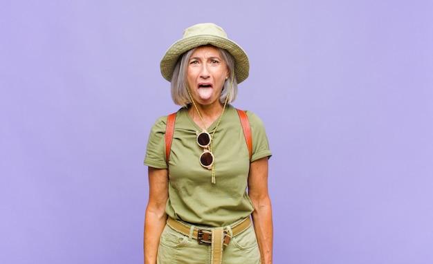 쾌활하고 평온하고 반항적 인 태도를 가진 중년 여성, 농담하고 혀를 내밀고, 재미