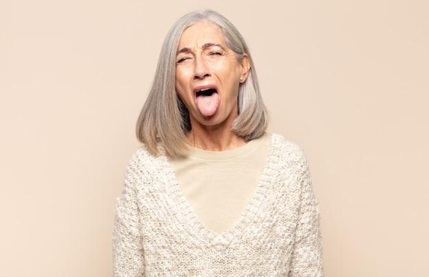 陽気な、のんきな、反抗的な態度、冗談を言ったり、舌を突き出したり、楽しんでいる中年の女性