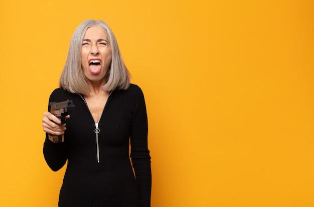 Женщина среднего возраста с веселым, беззаботным, бунтарским настроем, шутит и высунул язык, веселится