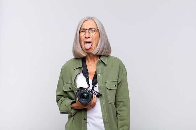 Middle age woman with cheerful, carefree, rebellious attitude, joking and sticking tongue out, having fun. photographer concept