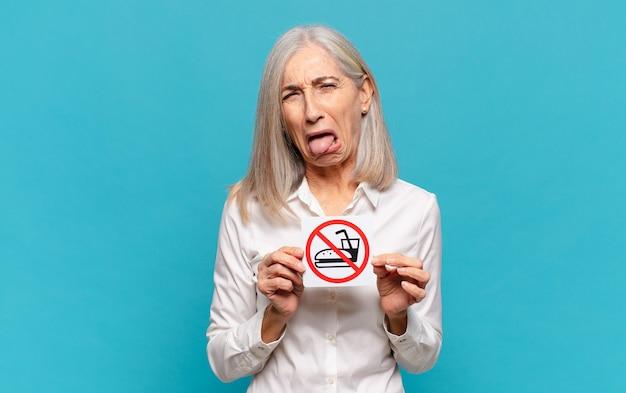 Женщина среднего возраста с вывеской не ест
