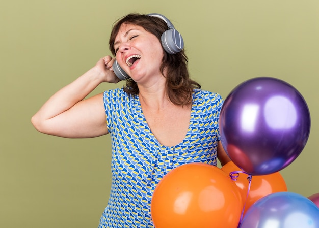 彼女のお気に入りの音楽を楽しんで幸せで陽気なヘッドフォンとカラフルな風船の束を持つ中年の女性