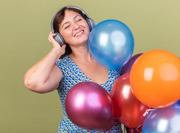Donna di mezza età con le cuffie e un mucchio di palloncini colorati felice e allegra che si gode la sua musica preferita