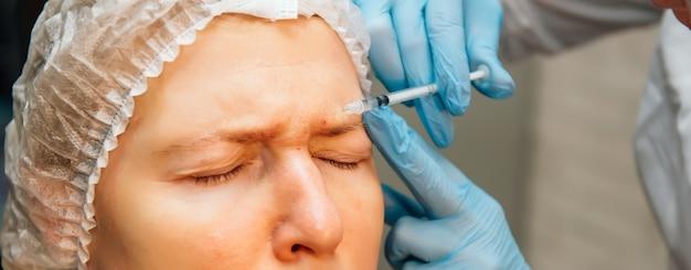 불완전한 피부를 가진 중년 여성이 이마 주름 제거를 위해 보툴리눔 독소 주사를 받고