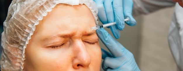 Middle age woman with imperfect skin getting botulinum toxin injections for removing forehead wrinkles