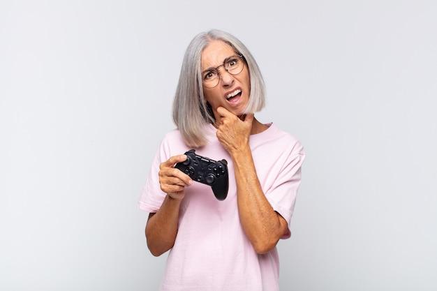 Женщина средних лет с широко открытыми глазами и ртом, положив руку на подбородок, ощущает неприятный шок, говорит что или ничего себе. концепция игровой консоли