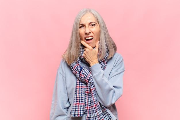 Женщина среднего возраста с широко открытыми глазами и ртом, положив руку на подбородок, чувствуя неприятный шок, говорит что или вау