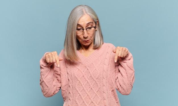 Женщина среднего возраста с открытым ртом, направленным вниз обеими руками, выглядела шокированной, удивленной и удивленной