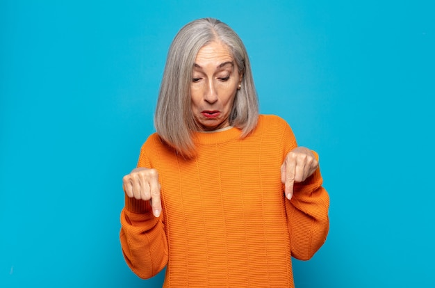 Middle age woman with open mouth pointing downwards with both hands, looking shocked, amazed and surprised