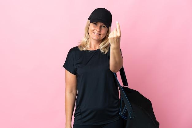 Женщина среднего возраста со спортивной сумкой, изолированной на розовом, делает приближающийся жест