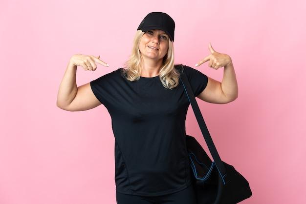 제스처를 엄지 손가락을주는 분홍색 벽에 고립 된 스포츠 가방 중년 여성