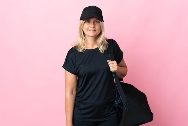 측면을 찾고 분홍색 벽에 고립 된 스포츠 가방 중년 여자