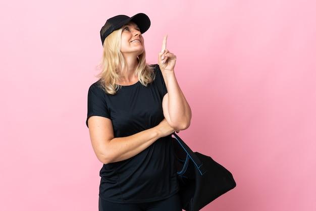 좋은 아이디어를 가리키는 분홍색 벽에 고립 된 스포츠 가방 중년 여성