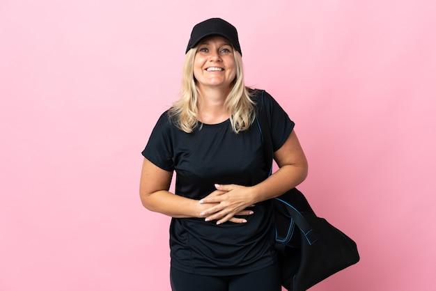 스포츠 가방 중년 여자는 많이 웃고 분홍색 벽에 고립