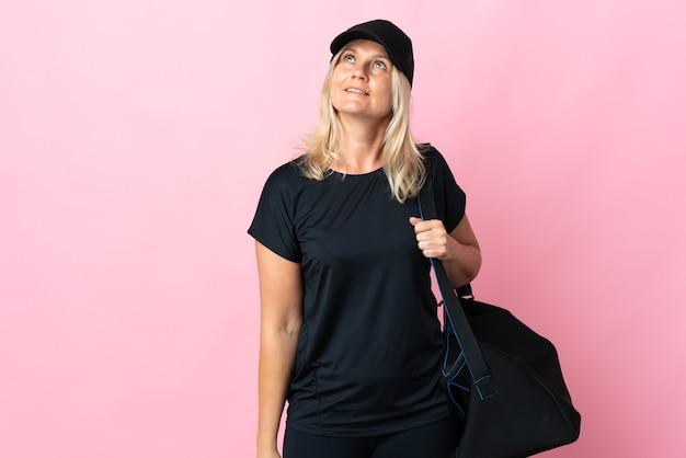 찾는 동안 아이디어를 생각하는 분홍색 벽에 고립 된 스포츠 가방 중년 여자