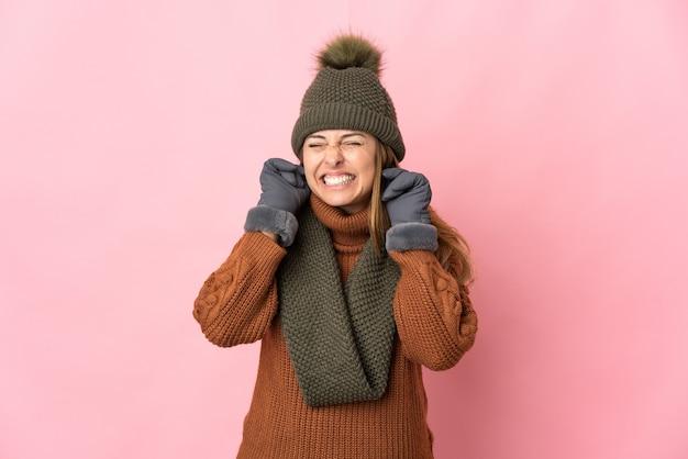 분홍색 배경에 고립 된 겨울 모자와 중년 여자는 좌절과 귀를 덮고