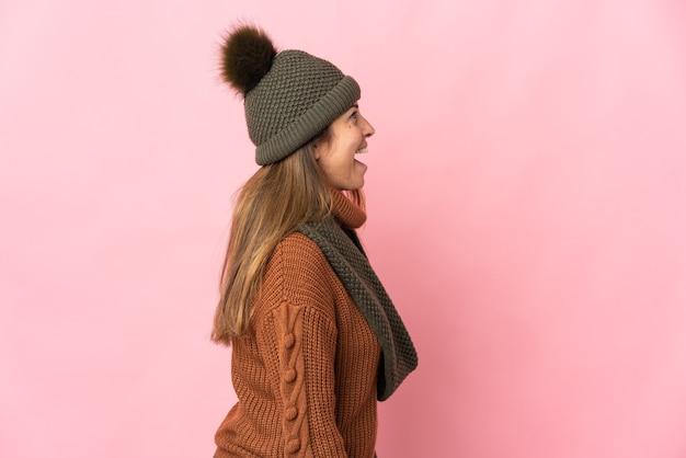 측면 위치에서 웃고 분홍색 배경에 고립 겨울 모자와 중년 여자