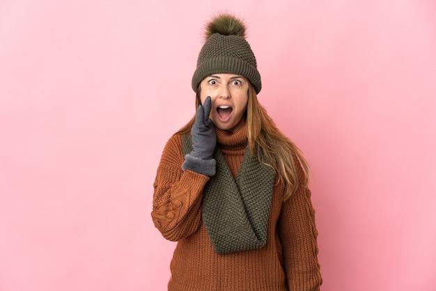 입 벌리고 외치는 분홍색 배경에 고립 겨울 모자와 중년 여자