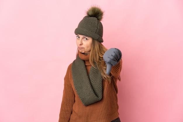 부정적인 표현으로 아래로 엄지 손가락을 보여주는 분홍색 배경에 고립 된 겨울 모자와 중년 여자