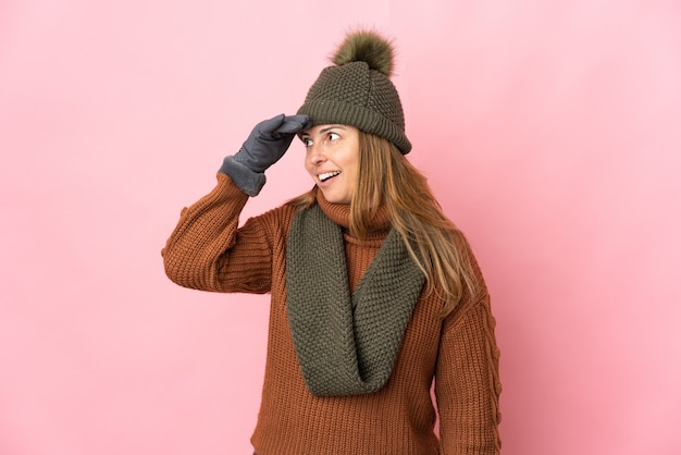 Middle age woman with winter hat isolated on pink wall doing surprise gesture while looking to the side