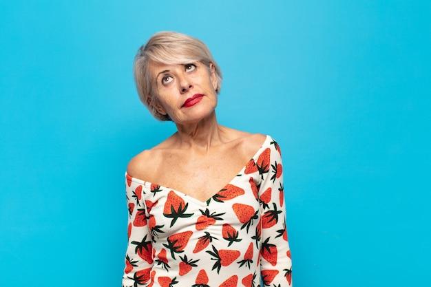 Женщина среднего возраста задается вопросом, думает о счастливых мыслях и идеях, мечтает, ищет, чтобы скопировать пространство на стороне